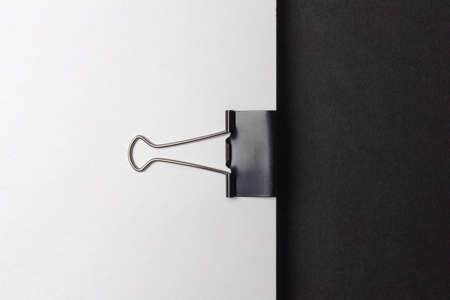 Stationery clip on clean white paper and black background. Minimalistic office work style