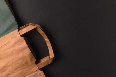 Paper shopping bag with handles on a dark background with space for text and advertising 版權商用圖片