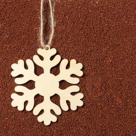 Christmas wooden snowflake on a background of ground coffee. Festive coffee mood