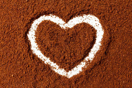 Hand drawn heart on a layer of ground coffee
