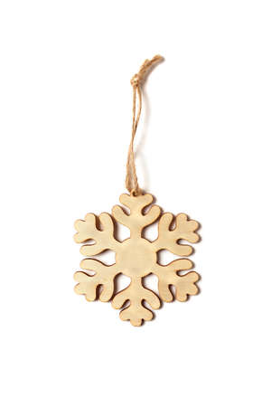 Wooden snowflake carved from wood with twine on a white background. Christmas decor and decorations