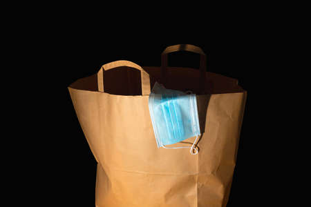 Large paper shopping bag with handles and a medical mask on a black background. Crisis concept 版權商用圖片