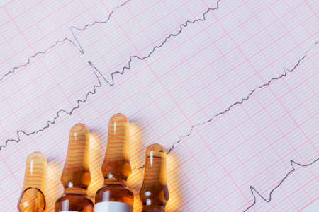 Medical ampoules on a cardiogram with indications of heart rhythms 版權商用圖片