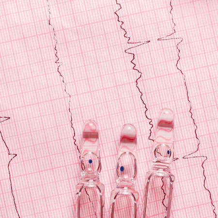 Ampoules with medication on an ECG with a heart schedule