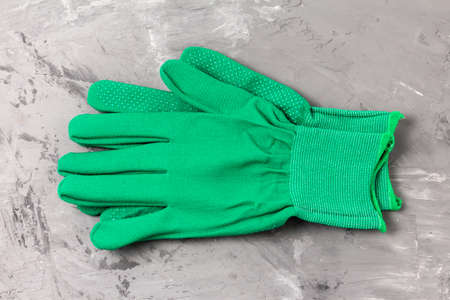 Two green work gloves with a protective layer on the palms and fingers on a gray cement background. Personal protective equipment against mechanical damage