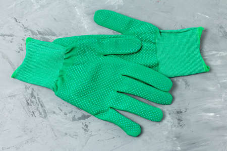 A pair of new protective cloth green household gloves on a gray concrete background. Close-up top view 版權商用圖片