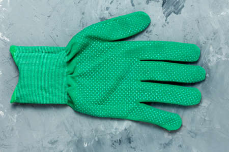 One clean blank green work glove on a gray concrete background. Protection of hands from mechanical damage