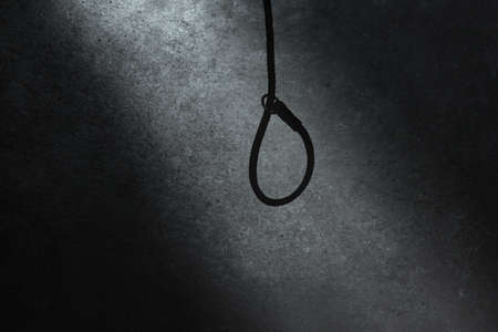 Hanging rope with a noose in the beam of light against the background of the dark gloomy wall of the dungeon. Gallows. Execution, stress and loneliness concept 版權商用圖片
