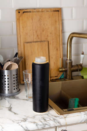 Old water filter cartridge in the kitchen on the background of sinks and dishes
