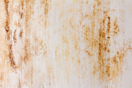 The white wall is stained with smudged streaks of rust