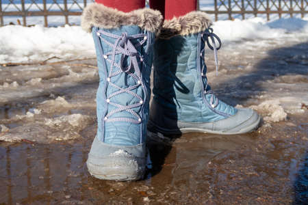 Children's feet in warm waterproof boots in a puddle from melting snow 版權商用圖片
