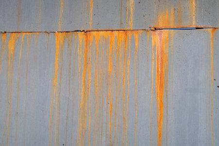 Rusty long parallel spots from rain erosion of steel. Rust on the metal sheet