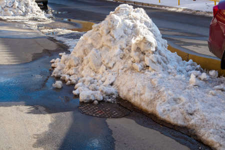 A pile of melting snow on the edge of the road and sidewalk 版權商用圖片