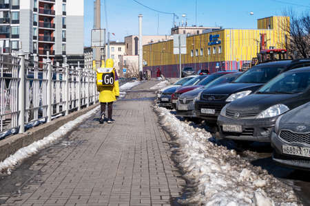 St. Petersburg, Russia - March 23, 2021: A Yandex food courier in a yellow uniform and a brand name with a thermal bag is walking along a city street with parked cars. Yandex Go - Delivery of groceries and ready meals from cafes and restaurants 新聞圖片