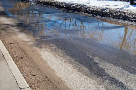 Dirty asphalt road with large puddles from melting snow and a layer of sand at the sidewalk. Consequences of de-icing urban roads in winter - dust and dirt from reagents and sand mixtures