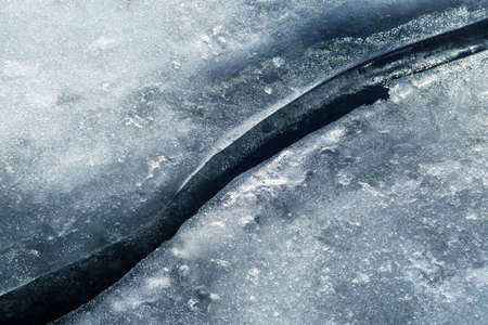 Top view of a dark spring winding stream between melting ice 版權商用圖片