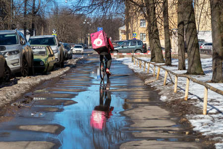 St. Petersburg, Russia - March 24, 2021: Unrecognizable courier on a bicycle delivers food in the city. Delivery man with fridge bag is reflected in a spring puddle on an empty street 新聞圖片