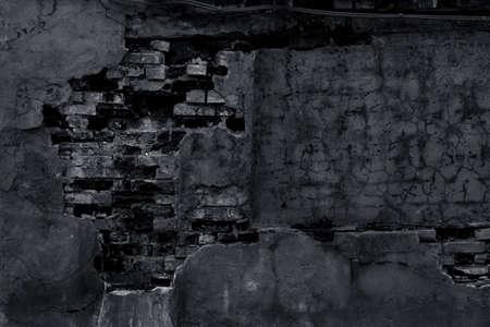 Old gloomy brick wall with peeling plaster and cracks. Dark night illumination of a graveyard stone fence. Grunge background