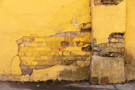 Old plastered yellow brick wall, scratched with cracks. Vintage background 版權商用圖片