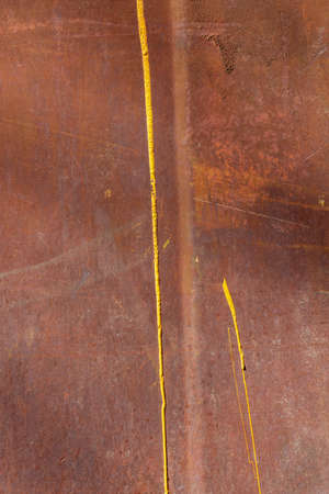 Traces of yellow paint on a rusty surface. Minimalistic industrial background. Streaks of dripping paint
