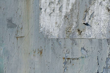 Remains of a paper notice on an old scratched wall. Industrial texture