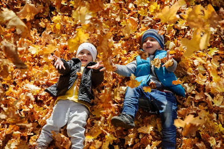 Happy children in autumn park lying on yellow maple leaves and trying to catch the falling leaves