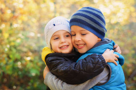 Happy embracing children, walking in the autumn park Banque d'images