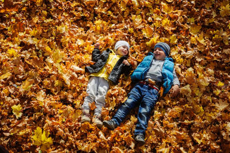Happy children in autumn park lying on yellow maple leaves Banque d'images