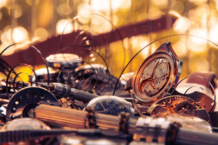 Composition of the old broken watches, with protruding springs and tools on a background of yellow bokeh
