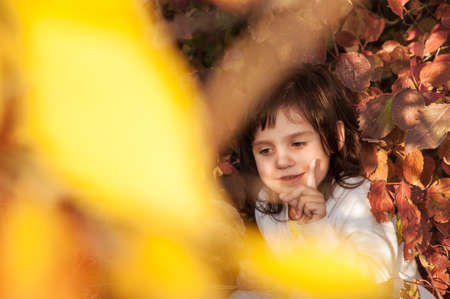 Cute little girl shows an attention sign, sitting under the shade of a tree in autumn park