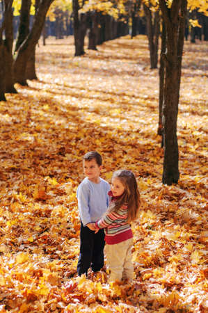 Smiling kids walk in the autumn park, stand and holding hands