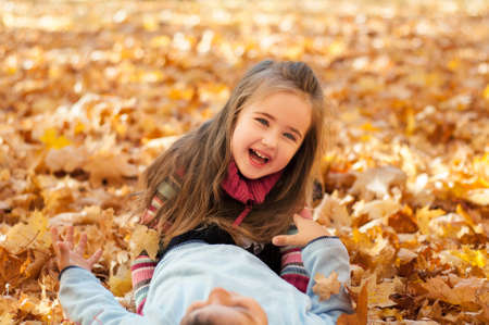 Happy children in autumn park lying on yellow maple leaves, little girl lies on a boy and laughing Banque d'images