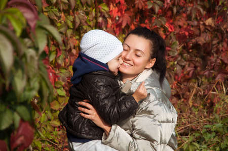 Happy mother and daughter embracing each other on the background of colorful autumn leaves of grapes