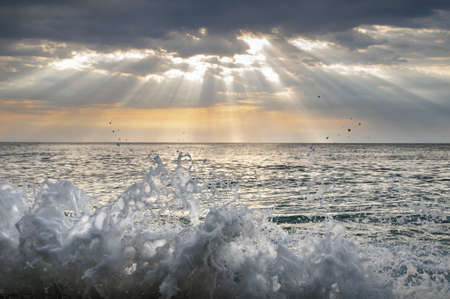 splashes of sea water and the sun's rays pass through the clouds