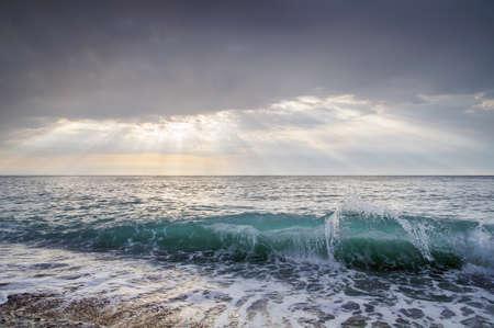 바다 파도와 태양 광선이 구름을 통해 통과
