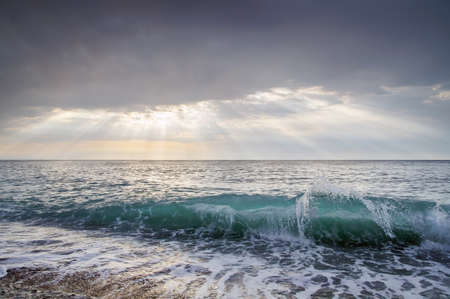 Sea wave, and the sun's rays pass through the clouds