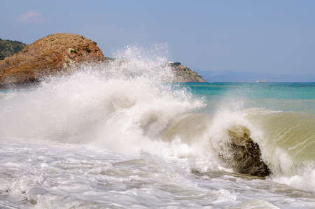 Big sea wave breaking on the shore and left behind huge parts of foam and spray Banque d'images