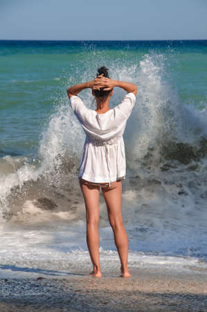 Young woman stands on the beach and put her hands to herself on the head and looks at the raging waves