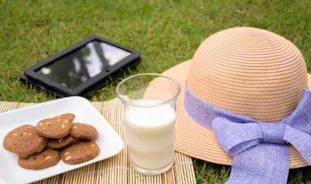 rest day in the garden with cookie, milk and tablet Stock Photo