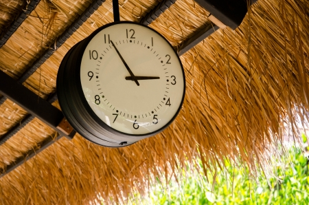 the clock hanging on the thatch roof
