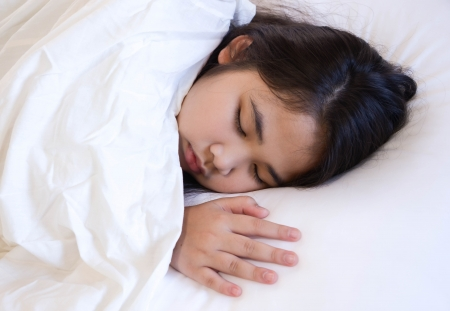 Cute young girl sleeping on a bed with white blanket and pillow.