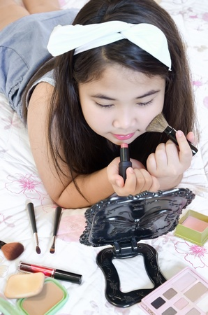 Little girl playing with mothers makeup on the bed. photo