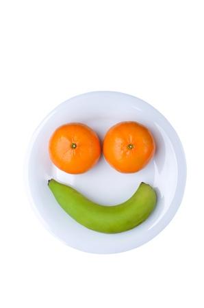 frutas divertidas: cara diversi�n fruta con pl�tano y naranjas, en un plato blanco.