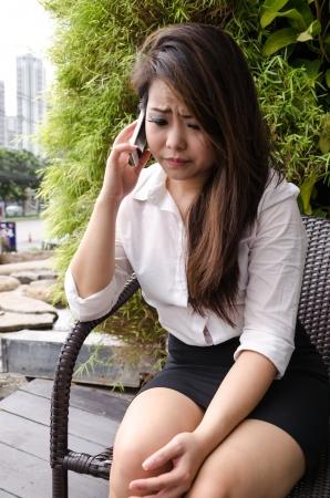 Joven mujer de negocios hablando por su tel�fono m�vil al aire libre, fondo del �rbol. photo