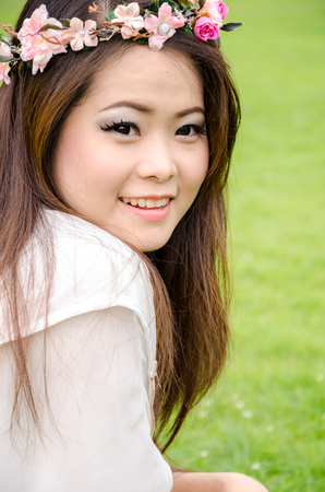 beautiful young brunette woman on the meadow with her flower chaplet