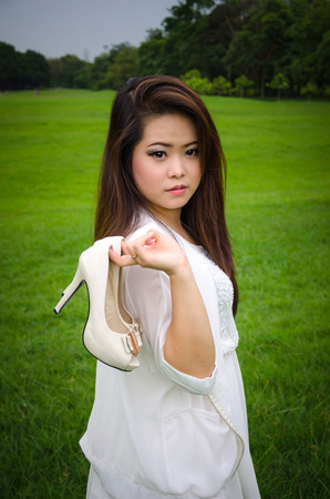 Beautiful young woman holding shoes, meadow background