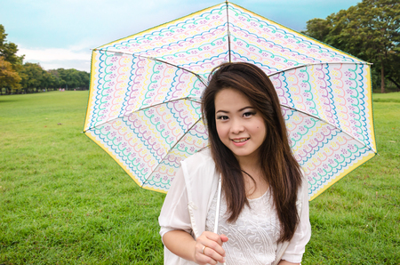 beautiful young brunette woman on the meadow with cute umbrella Stock Photo