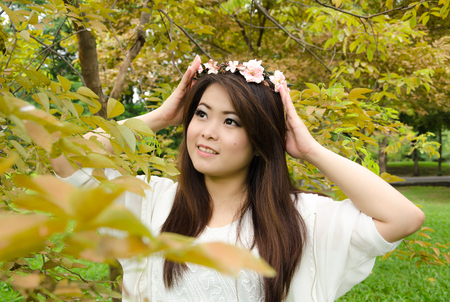 beautiful young brunette woman in the park with her flower chaplet