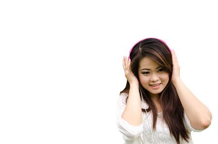 Beautiful woman listening the music through headphones, white background