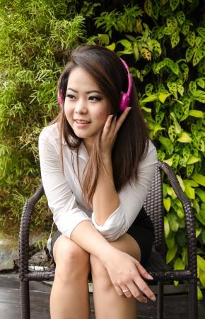 Relax business woman listening the music through headphones, outdoor